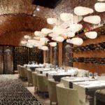 la foto rappresenta la sala ristorante, con la volta a botte in mattoni medioevali. le sedute sono in pelle e i rivestimenti parietali in legno e vetro a decori geometrici retroilluminato.
