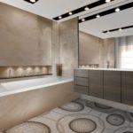 bagno con vasca incassata e mobile lavello appeso. il pavimento è in mosaico
