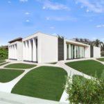 casa in stile miminalista a forma di rettangolo ad un piano inserita in un giardino con camminamenti e sentieri dalel forme organiche